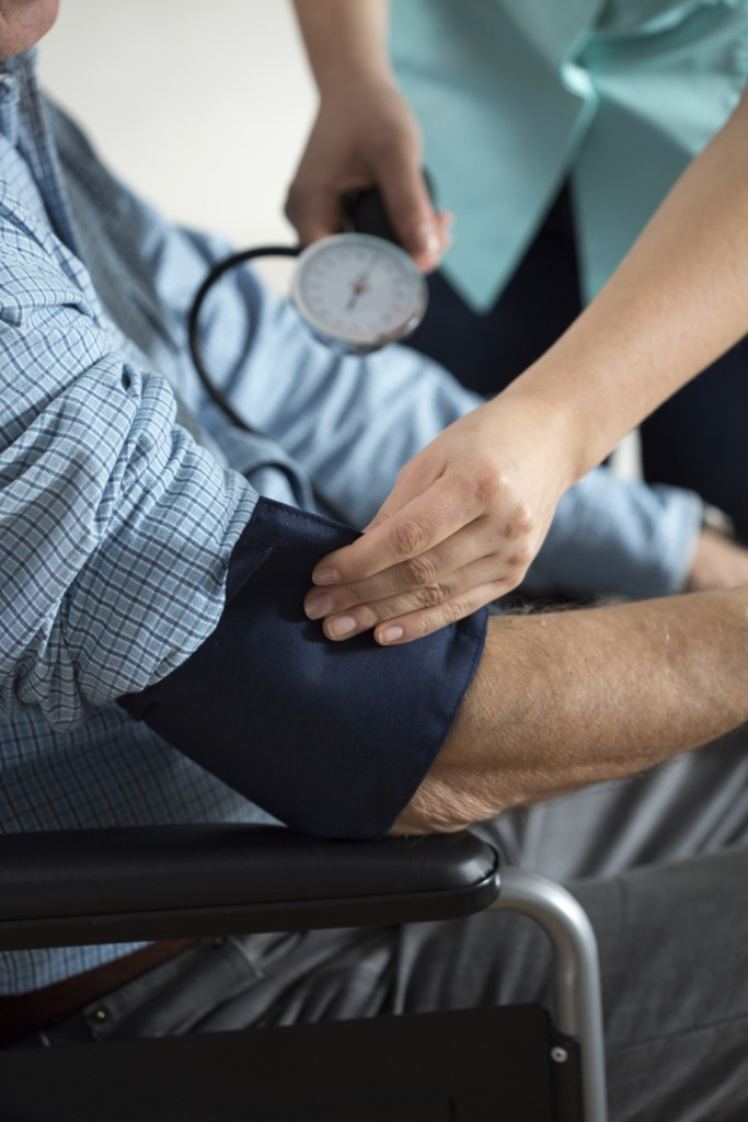 Close-up of disabled man and nurse using sphygmomanometer